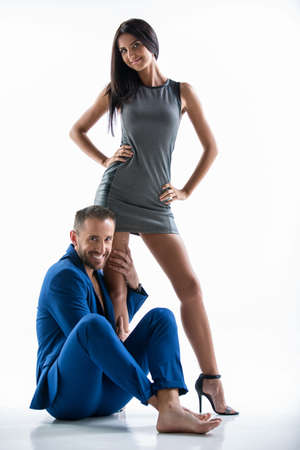 leggy girl: Positive couple in the studio on a white background. Leggy girl with dark hair standing in a short dress. A man with a beard wearing a blue suit sitting on the floor.She hugs her leg