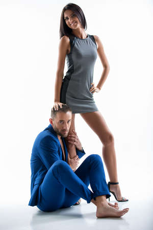 leggy girl: Young couple in the studio on a white background. Leggy girl with dark hair standing in a short plate.Polozhila hand on the mans head. A man with a beard wearing a blue suit sitting on the floor.She hugs her leg Stock Photo