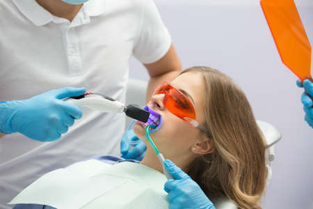 Girl patient in the dental clinic. Teeth whitening UV lamp with photopolymer composition. Standard-Bild