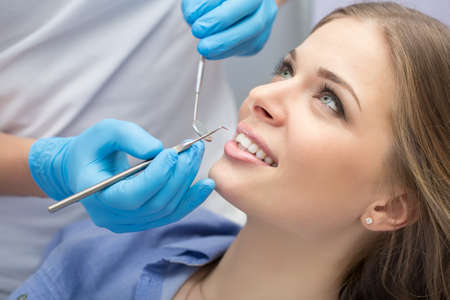 Girl with beautiful white teeth on reception at the doctor dentist.