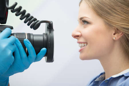 Dentist with camera making shots of patients smile after treatment. Special camera with flash ring shadowless. Foto de archivo