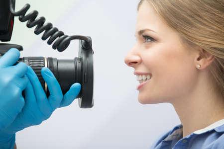 Zahnarzt mit Kamera Herstellung Aufnahmen von Patienten Lächeln nach der Behandlung. Spezielle Kamera mit Blitz Ring schattenlos. Standard-Bild - 51062331