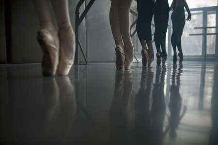 bare girl: Group of ballet dancers stands near the ballet barre at the ballet hall against the big window. Daylight falls on them. Shoot from a low angle. Stock Photo