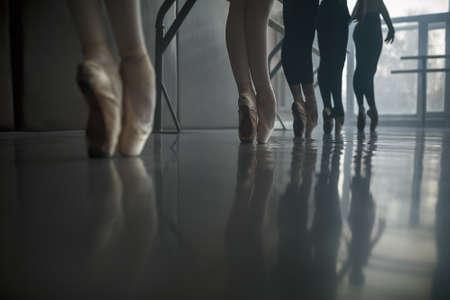 Gruppe der Balletttänzer steht in der Nähe der Ballettstange an der Ballettsaal gegen das große Fenster. Tageslicht fällt auf sie. Schießen von einem niedrigen Winkel.