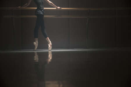 Ballerina standing on pointes. She puts her hands on a barrel. Light falls from above on her. Photo without face.