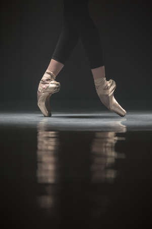 pointes: Legs of ballerina who stands on the pointes. Light falls down on her feet. Photo shoot in a low key. Stock Photo
