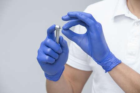 Dentiste dans les gants de latex bleu et t-shirt blanc tenant la pièce à main dentaire avec fraise dentaire dans ses mains. Studio photo sur le fond gris. Horizontal.