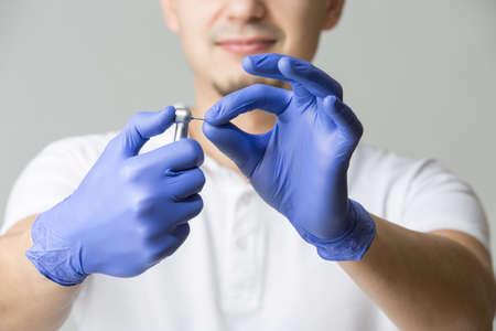Docteur en gants de latex bleus et t-shirt blanc tenant la pièce à main dentaire avec une fraise dentaire dans ses mains. Studio photo sur le fond gris. Horizontal.