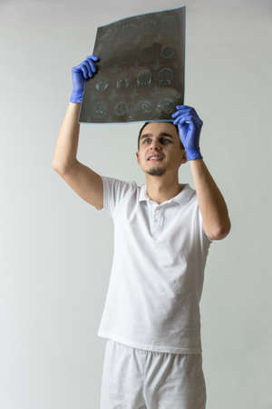 tomography: Young doctor in white uniform and blue latex gloves holds a tomography results in his hands. He looks at the tomography results. Studio photo on a gray background. Vertical.