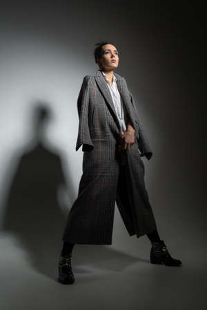 legs apart: Girl in full growth standing on a gray background in a studio. She is standing with her legs apart and holding her hands together in front of her. She dressed in a long coat with patterns. Shoot in a low key. Vertical.