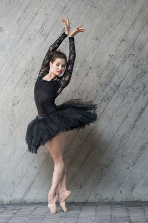 pointes: Beautiful ballerina standing on the pointes with outstretched hands up. She dressed in the black dance suit with black tutu. Full growth photo outdoors. Vertical. Stock Photo