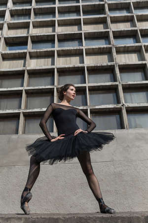 animal tutu: Pretty ballerina posing on the concrete wall background. She holds her hands on the belt while one leg stands on the toe. She dressed in the black dance suit with black tutu and pointe shoes. Full growth photo outdoors. Vertical. Stock Photo