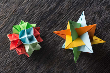 design objects: Flower and star kusudama origami on the textured surface. Star origami colored in green, blue, yellow and orange. Flower origami colored in green, red and blue. Close-up photo. Horizontal. Stock Photo