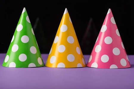 Few party hats on a violet surface on the dark reflective background. Hats are green, yellow, pink and all in white peas. Close-up photo. Horizontal.