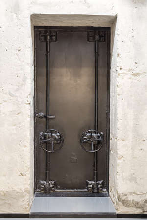 doorhandle: Metal old door with two valves and a doorhandle. Its in the concrete wall. Verical.