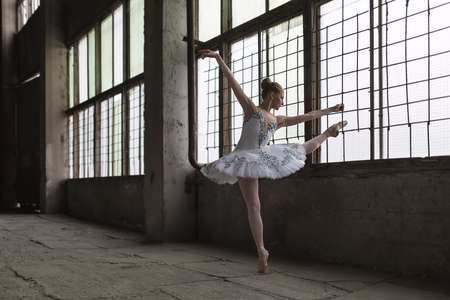 pointes: Handsome ballet dancer posing in front of windows in an old industrial building. She dressed in a white tutu and pointes. She stands on one leg with outstretched towards hands and the second leg. Indoor. Horizontal.