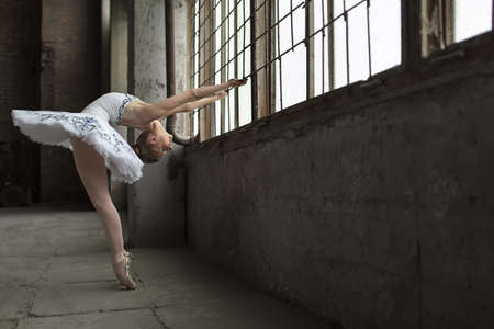 pointes: Young ballet dancer posing next to windows in an old industrial building. She is standing on pointes while she holds the grille during tilting back. Indoor. Horizontal. Stock Photo