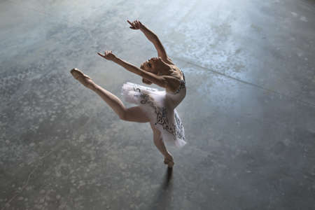 Pretty ballerina in a white tutu making a pose in a hall. She outstretches her hands and one leg up during tilting back. Daylight falls on her. Indoor. Horizontal.
