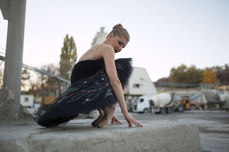 black toes: Young ballerina sitting on her toes resting on the fingers. She is wearing a black tutu and sitting on a concrete structure. Behind her is a parking for technical cars. Outdoor. Horizontal.