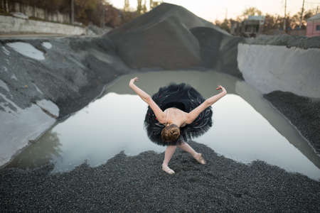 reverence: Beautiful ballerina making a reverence on gravel in front of ditch of gravel with water. She wears a black tutu and a ballet shoes. There are railway rails on the right side. Outdoor. Horizontal.