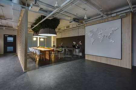 Room in a loft style. There are light and dark tables, light and dark chairs. There is stand for office supplies between light tables. Above them hang large lamps with artificial leaves. A few laptops are on the table. On the right there is a wall with wo Foto de archivo