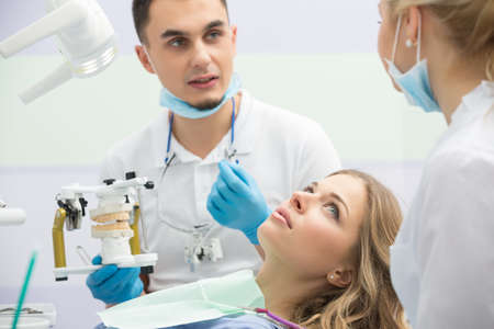 articulator: Young dentist working with the patient in a modern hospital. He is assisted by a young girl assistant.