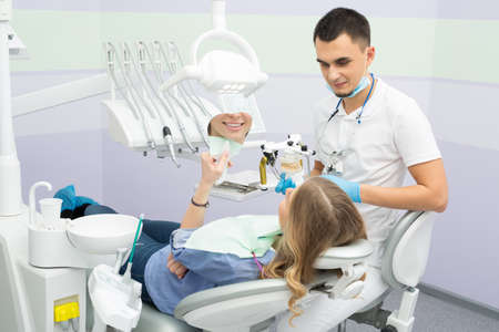 articulator: Young dentist working with the patient in a modern hospital. He is assisted by a young girl assistant. The patient sees in the mirror the result of the work of the doctor.