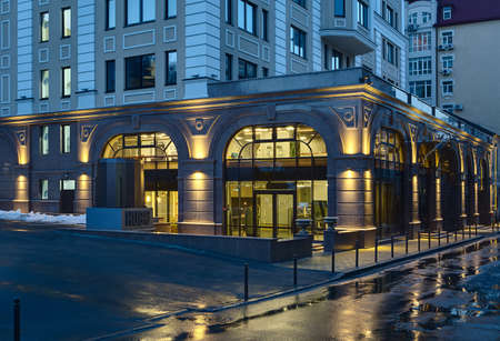 carriageway: Facade of the building with entrance to coworking in the twilight. Coworking is on the first floors. Indoors lights are on. In front of building there are wet sidewalk and carriageway with puddles. Stock Photo