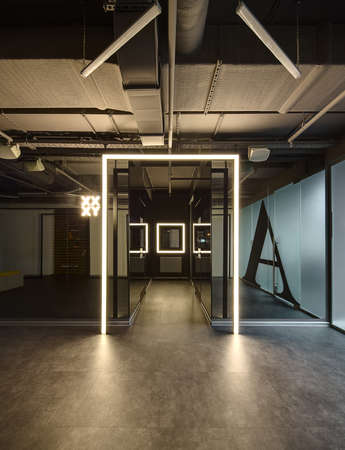 allocated: Loft style interior. Mirrored walls with reflected parts of the room in it. Between the walls there is a corridor with doors on each side and a luminous window frame at the end. Start of corridor allocated by luminous frame. There is a luminous pointer on