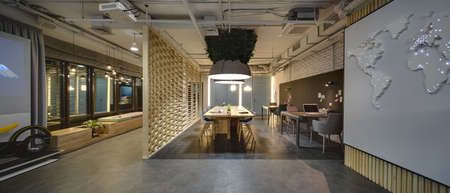 Interior in a loft style. There are tables and chairs. There are notebooks, laptops, holders with pens and grass decoration on the tables. Above them hang large lamps with artificial leaves. A few laptops are on the table. On the right there is a wall wit Standard-Bild