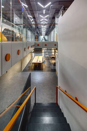 wooden partition: Interior in a loft style. Top view of the black stairs with orange handrails. On the right there is a gray wall. At the end of the 1st floor there are a zone with tables and chairs and big lamps. Also there is a ornamental wooden partition on the left of