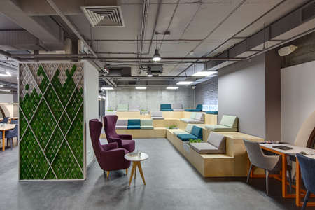 Interior in a loft style with a big zone with wooden benches and seats. Benches are decorated with grass, plants and bricks. On the right there is a gray table with orange legs and two chairs. In the center there are two purple armchairs with small round  Фото со стока