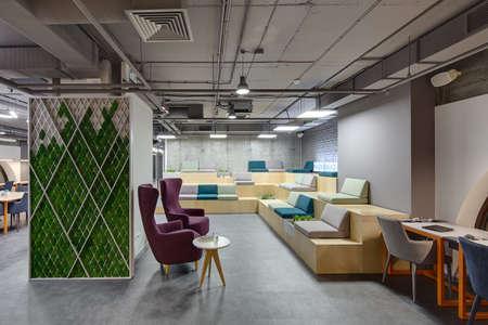 Interior in einem Loft-Stil mit einer großen Zone mit Holzbänken und Sitzplätzen. Bänke sind mit Gras, Pflanzen und Steine. Auf der rechten Seite gibt es eine graue Tabelle mit orange Beine und zwei Stühlen. In der Mitte gibt es zwei lila Sessel mit kleinen runden Standard-Bild - 54432729