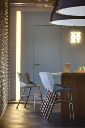 wooden partition: Table with a laptop on it and chairs standing near the table. Two large lamps over the table. On the left there is an ornamental wooden partition. On a background there are a wall with a door and a glowing pointer. Place for coworking.