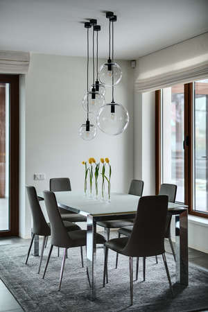legs around: Room with light walls. On the floor there are gray tiles and a gray carpet. On the carpet stands table with frosted glass tabletop and chromed legs. On the table stand 5 glass vases with yellow tulips. There are 6 gray chairs with chromed legs around the  Stock Photo