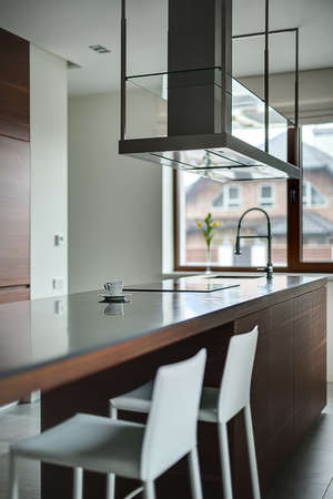 range hood: Brown kitchen island with cooktop, sink and modern range hood over it on the brown window background. Walls are light. There is a white cup with saucer on the tabletop. Two white chairs are near the kitchen island. On the floor there are gray tiles. Soft