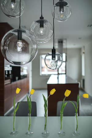 vertical: Five yellow tulips in glass vases on the table and five glass round lamps over them. They are on the soft background of brown kitchen with light walls. Vertical. Stock Photo