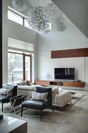 pillow: Hall in a cottage with light walls and big round ornamental lamps at the top. In the centre there are two black armchairs with gray pillows, beige sofa with pillows and dark table. On the left there is a brown glass door and a window with blinds, brown wi