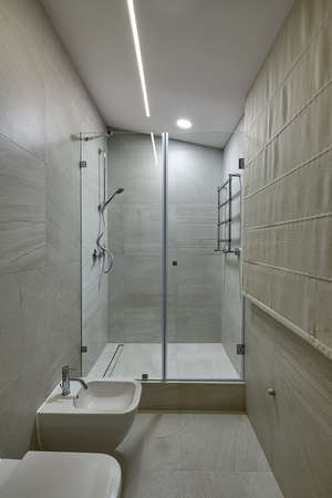 bidet: Shower room with shower cabin with glass door, white bidet and white toilet. Room overlaided with light tiles. In the shower cabin there is a shower on the left and a towel rail on the right. On the right there are blinds. At the top there are lamps. Stock Photo