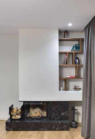 stone fireplace: Light room with black stone fireplace with glass door and white chimney. On the right of the chimney there are wooden shelves with books, a candle and an old airplane model. There is a pack of firewoods on the left of fireplace and a set of fireplace poke Stock Photo