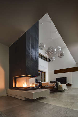 Hall in a cottage with light walls and big round decorative lamps at the top. In the front there is a glass fireplace with burning fire and a black chimney. Behind the fireplace there are two black armchairs with gray pillows, beige sofa. At the end on th