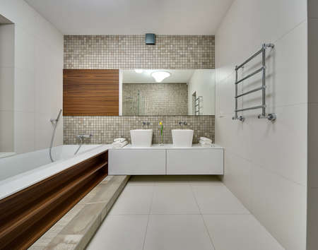 niches: Bathroom in a modern style with light tiles on the walls and floor. On the left there is a white bath with wooden niches on the right side. On the right wall there is a towel rail. On the back wall there is a rack with two white sinks, white towels and a