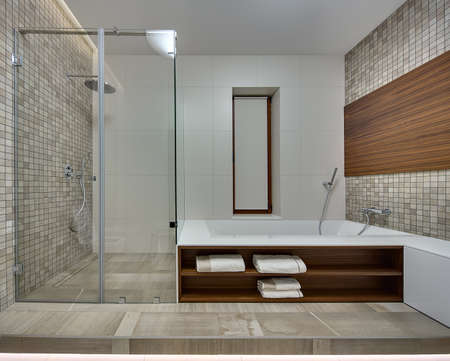 niches: Bathroom in a modern style with light tiles on the back wall. Side walls is decorated with brown-beige mosaic  and a wooden panel. On the right there is a white bath with wooden niches. There are towels in the niches. On the left wall there is a shower ca