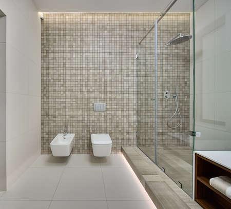 cabine de douche: Salle d'eau dans un style moderne. Paroi arrière décorée de mosaïque beige. Sur le mur arrière, il y a un bidet blanc, toilette et commutateurs blanc. Sur la droite, il y a une cabine de douche avec des carreaux texturés beige sur le sol. Sur les parois latérales et le plancher, il y a li