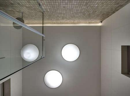 cabine de douche: plafond blanc dans une salle de douche avec des lampes arrondies. Une lampe refl�te dans le c�t� de verre d'une cabine de douche. Les parois lat�rales sont de tuiles l�g�res. paroi arri�re est orn�e de mosa�que beige.