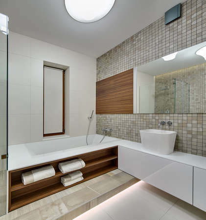 wall light: Bathroom in a modern style with light tiles on the left wall and floor. On the left there is a white bath with wooden niches with towels. On the right there is a white rack with white sink. Right wall is decorated with brown-beige mosaic, wooden panel and