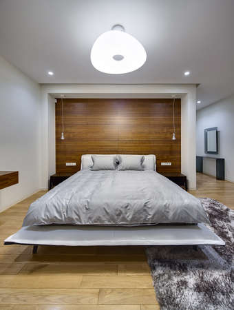 bedcover: Bedroom in a modern style with light walls. There is a big bed with gray bedcover and pillows. On the both sides of the bed there are dark wooden bedside tables. On the back wall there is a big niche with wooden panel, hanging lamps and switches with powe Stock Photo