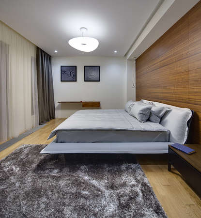bedcover: Bedroom in a modern style with light walls. There is a big bed with gray bedcover and pillows. On the right side of the bed there is a dark wooden table with a book. On the right wall there is a big niche with wooden panel and hanging lamp. On the back wa