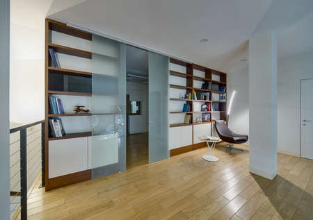 sliding doors: Hall with light walls and a light parquet on the floor. There are brown-white bookcases with books and models of old airplane and bike. Between the bookcases there are frosted glass sliding doors. Big white ornamental round lamps reflected in the doors. B