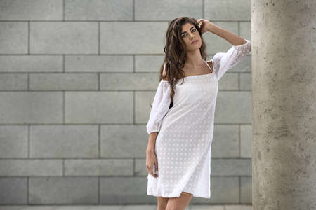 leans on hand: Pretty girl stands near the concrete column on the background of the wall with tiles. She wears the white dress with dots. Her left elbow leans on the column while hand is on the her head. She looks into the camera. Horizontal.